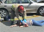 Photo of firefighter checking the pulse of a teenaged female accident victim in a mock crash
