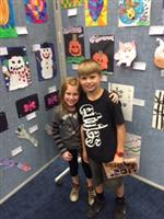Photo of an elementary age boy and girl standing against a wall of student artwork