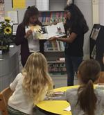 Photo of two junior high girls holding up a book for two elementary school girls to see