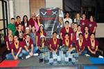Photo of several junior high students with awards and holding up robotics state championship banner