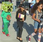Three elementary students dressed as a block head, Bat Girl, and in striped socks