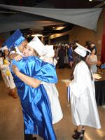 Two high school graduates, a boy and girl, embracing