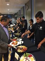 Photo of high school student serving food, buffet style, to adults