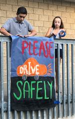 A high school boy and girl hang a poster from a second story railing. It says Please drive safely.