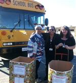 Photo of three women standing in front of school bus with two large cardboard boxes