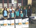 Photo of three young girls and five women manning a jacket drive