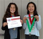 Photo of two female sixth graders, one holding a certificate, the other a medal