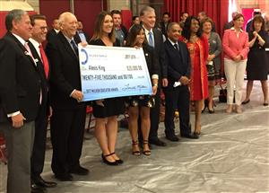 Several adults are standing and holding an oversized check for $25,000