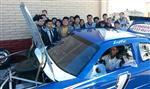 Several high school students standing behind a race car. One student is behind the wheel.