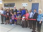 Several adults and four elementary students at a ribbon cutting in front of a modular building