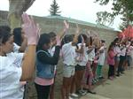 Photo of older elementary school students standing and waving their hands while wearing pink surgical gloves