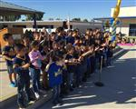 Photo of several kindergarten students singing at an outdoor assembly