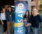 Two adult women and two eighth-graders, boy and girl, stand on either side of a banner that says RIMS AVID