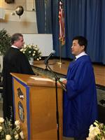 Photo of adult graduate leading the Pledge of Allegiance, while Principal Carl Hamton faces the American flag.