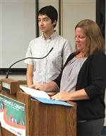 Photo of teenage girl and woman at a podium.
