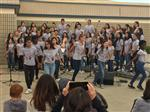 A large group of junior high girls sing and dance in a school quad as the audience takes photos