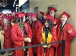 Photo of a small group of high school graduates waiting for their commencement to begin