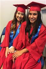 Photo of two female high school graduates in red caps and gowns, sitting on chairs and smiling.