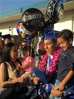 Photo of male high school graduate holding a balloons and a little boy. Standing nearby is a young woman holding a baby girl.