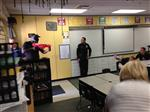 Photo of police officer looking at a mock intruder with a toy gun, entering a classroom