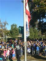 Photo of 2015 National Blue Ribbon flag being raised at Country Springs Elementary, with students and parents in background