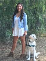 Teen girl with long brown hair holding the leash of a white Labrador Retriever puppy.