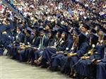 Many high school graduates sitting in chairs, holding white roses