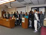 Photo of high school basketball team inside school board room