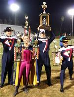 Photo of four Chino High Band members in uniform, holding trophies