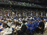 Photo of Chino High Graduation Ceremony: graduates on floor of Arena, with families in surrounding stands.