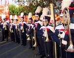 Photo of approximately nine Chino High Band members in uniform and with brass instruments.