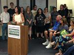 Photo of Chino High math teacher Diane Murillo at a podium. She is flanked by her former high school students.