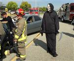 Photo of high school student dressed as the Grim Reaper, walking past a mock car accident and firefigher and camerman.