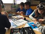 Photo of four or five students working on a prosthetic hand