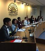 Photo of seven high school students sitting at the School Board dais