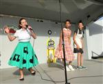 Junior High girl in 1950s costume sings while two others listen to her, all are on a stage