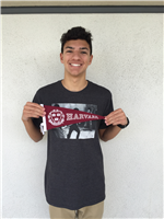 Male high school student holding Harvard pennant