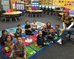 Photo of female transitional kindergarten teacher in classroom with 11 of her students