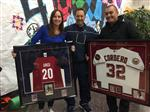 Three adults, two holding framed sports jerseys