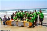Photo of large group of people in green wetsuits at the beach, standing behind a surfboard