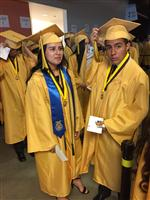 Photo of two high school graduates -- girl and boy -- iin gold caps and gowns. Other graduates behind.