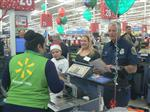 Photo of a Walmart cashier checking out a boy and this mother, as a firefighter prepares to pay the bill