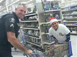 Photo of Chino Police Officer and elementary student in a Santa hat, shopping in Walmart