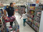 Elementary age girl points at a board game in a big store, while a male firefighter behind a shopping cart looks on