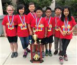 Seven fourth-graders, all wearing red shirts and medals, stand behind a large trophy