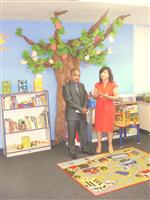 Superintendent Wayne Joseph and Liz Lara standing inside a room, filled with a fake tree, bookcase, and child's play rug