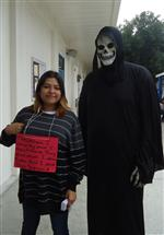 Photo of teen girl standing next to person dressed as the Grim Reaper