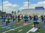 Students striking a yoga pose in front of Chino High Stadium bleachers